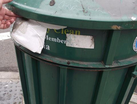 Garbage cans along Queens Blvd have stickers covering up the name of the former Councilman who purchased them. (photo credit: azi paybarah)
