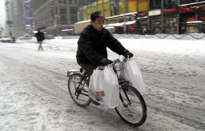 A delivery man pedals through the aftermath of a winter storm in February 2003 (Photo: Graham Morrison/Getty Images).
