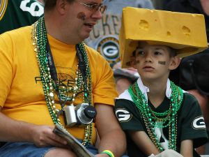 "A pair of Wisconsin football fans cheering on the Green Bay Packers in their trademark ""cheeseheads."""