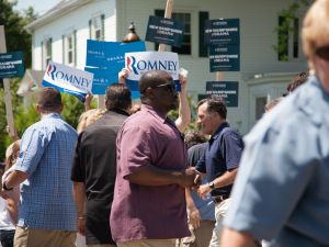 Mitt Romney shaking hands as his supporters held signs in front of Obama signs at the parade in Wolfeboro.