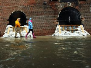 NEW YORK, NY - OCTOBER 29: People walk past sandbags on a flooded street as Hurricane Sandy moves closer to the area on October 29, 2012 in the Red Hook section of the Brooklyn borough of New York City. The storm, which threatens 50 million people in the eastern third of the U.S., is expected to bring days of rain, high winds and possibly heavy snow. New York Governor Andrew Cuomo announced the closure of all New York City bus, subway and commuter rail service as of Sunday evening. (Photo by Spencer Platt/Getty Images)