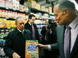 Senator Schumer attempts to hand some cereal to Mayor Bloomberg. (Photo: Getty)