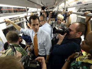 Anthony Weiner rides the train with some press. (Photo: Getty)