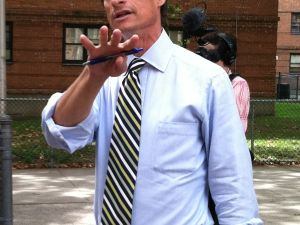 Anthony Weiner motioning to a public housing complex that went up in flames.