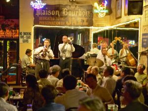 Maison Bourbon Jazz Club with Dixieland band and trumpet player performing at night in French Quarter in New Orleans, Louisiana.