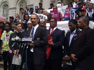 Center for Constitutional Justice Attorney Darius Charney stands beside stop and frisk reform advocates during conference today.