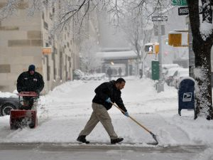 Harlem residents clear snow for the umpteenth time this week. STAN HONDA/AFP/Getty Images