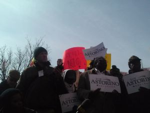 "Protesters wave signs like ""Astori-NO!"" behind Mr. Astorino as he speaks."