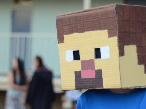 A Minecraft enthusiast above wears a headpiece depicting the Minecraft avatar, which is the only total immersion experience available for the foreseeable future.  (photo: Andrew Beeston, CC BY 2.0)