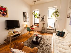 The living room, featuring a portrait by Craig Redman. (<em>Photo by Emily Assiran</em>)
