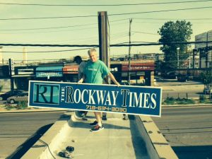 Kevin Boyle, owner and editor of the Rockaway Times, gets ready to publish his first issue next week, putting the sign up in front of his bare bones office. (Courtesy of Kevin Boyle)