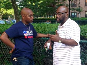 Pastor Mike Walrond listens to a potential voter on 108th Street and First Avenue.