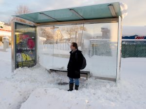 A man waits at a bus stop in the Bronx. (Photo via Getty Images)