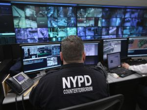 An NYPD officer watches security camera footage.