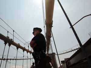 Police walk along the Brooklyn Bridge following the discovery of a pair of white flags that appeared there July 22. (Photo by Spencer Platt/Getty Images)