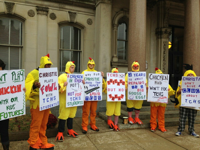 Protesters festooned in rooster garb on Halloween charge Christie with being 'chicken'