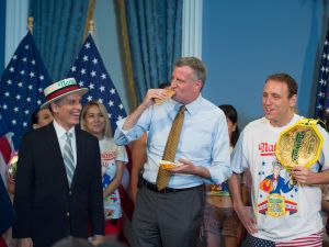 Mayor Bill de Blasio eats a hot dog between contest co-founder George Shea and Joey Chestnut. (Rob Bennett/Office of the Mayor)
