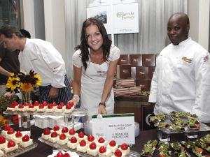 Chef Kerry Heffernan (left) prepares more samples as tennis pro Agnieszka Radwanska hands out Cheesecake Factory desserts and chef Jay Hinson looks on. (Photo via Getty)