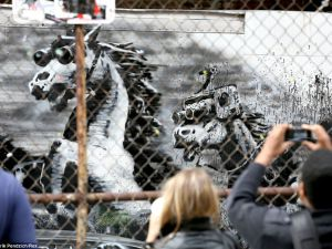 People taking pictures of a Banksy work. (Courtesy Banksy's website)