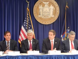 Andrew Cuomo, accompanied by Jeffrey Klein, Dean Skelos, and Sheldon Silver (Photo: Will Bredderman).