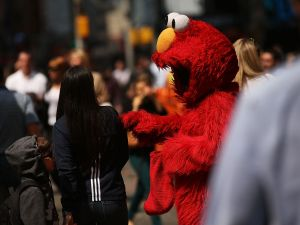 Elmo asks Times Square tourists for money.