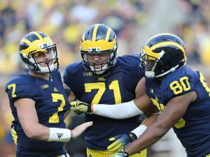 Quarterback Shane Morris #7 of the Michigan Wolverines is helped off the field by teammates. (Photo by Leon Halip/Getty Images)