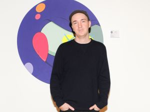 Brian Donnelly, also known as the artist KAWS, with his work at the 2014 RxArt Benefit. (Photo courtesy BFA)