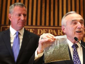 Mayor Bill de Blasio looks on as NYPD Commissioner Bill Bratton holds up a bag of oregano.