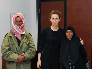 "The PR Firm Brown Lloyd James was paid a reported $5000 a month by the Syrian Government to manage a fawning Vogue profile for First Lady Asma al-Assad, pictured here in a shot from last October on the official Facebook page of the Syrian Presidency, ""posing for a picture with family members of martyrs"" in Damascus. (AFP/Facebook/Getty Images)"