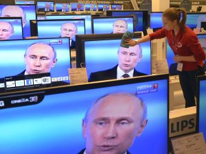 An employee wipes a TV screen in a shop in Moscow during a broadcast of President Vladimir Putin. (ALEXANDER NEMENOV/AFP/Getty Images)