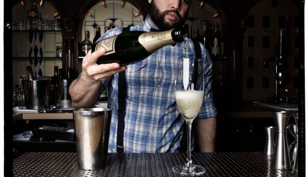 A bartender at Dear Irving pours a glass of bubbly. (Photo: Celeste Sloman/For New York Observer)