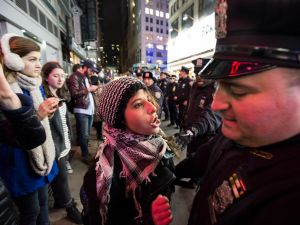 A protester confronted a member of the NYPD at a protest last year over the Eric Garner decision.