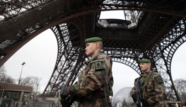 French soldiers patrol in front of the Eiffel Tower on January 7, 2015 in Paris as the capital was placed under the highest alert status after heavily armed gunmen shouting Islamist slogans stormed French satirical newspaper Charlie Hebdo in the deadliest attack in France in four decades. (JOEL SAGET/AFP/Getty Images)