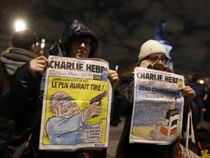 Women in Paris hold Charlie Hedbo's front pages as a tribute to the slain journalists.
