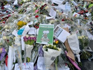 PARIS, FRANCE- Tributes of drawings, flowers, pens and candles are left in front of the Charlie Hebdo offices on January 14, 2015 in Paris, France.