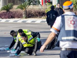 Israeli emergency services personnel clean the sidewalk at the scene of an attack after a Palestinian man stabbed at least five people on a Tel Aviv bus on January 21, 2015. (Getty Images)