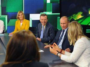 Vladimir Putin jokes around with RT talking heads (Photo: Wikimedia).