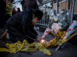A woman lights up a candle at the scene of a fire that killed seven children yesterday in the Midwood neighborhood March 22, 2015 in the Brooklyn borough of New York City. Investigators say a hot plate in the kitchen started the fire that killed the children ranging in age from five to 16 years old, and left the mother and another child in critical condition. The bodies of the children are being flown to Israel for burial. (Photo by Kena Betancur/Getty Images)