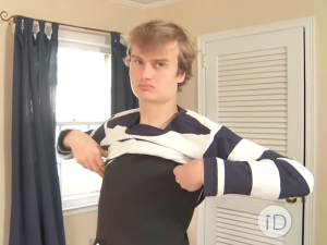 Liam putting on an ID Clothing shirt. (Screengrab:YouTube)