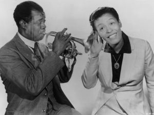 Billie Holiday pays close attention to Louis Armstrong. (Photo: Hulton Archive/Getty Images)