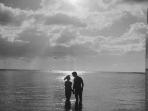 Circa 1955: a young couple on their honeymoon in Hawaii enjoy the romance of a sunset dip in the Pacific Ocean. (Photo: Orlando /Three Lions/Getty Images).