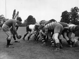 A rugby team gets in a scrum.