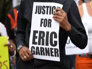 A protester holding a sign demanding justice for Eric Garner.