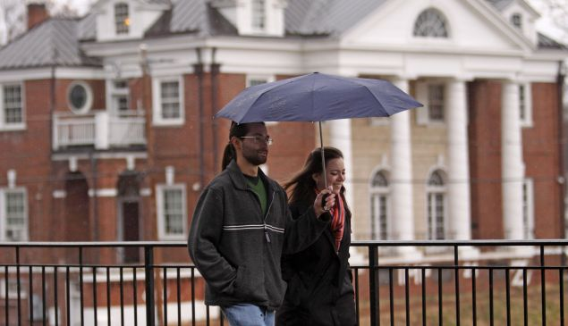 Students walk past the Phi Kappa Psi fraternity house at the University of Virginia.