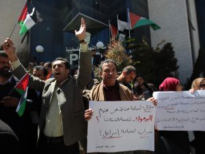 Palestinians shout slogans as they hold banners during a gathering in solidarity with the Palestinians living in Syria's Yarmouk camp, which is besieged by government forces and has been largely overrun by jihadist fighters, on April 5, 2015 outside Palestinian Liberation Organization (PLO) headquarters the in the city of Ramallah in the West Bank. AFP PHOTO / ABBAS MOMANI (Photo credit should read ABBAS MOMANI/AFP/Getty Images)