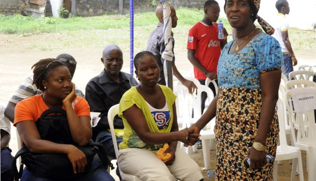 Beatrice Yordolo, who was declared the last survivor of the Ebola virus on March 5, 2015, shakes hands with family and neighbours during a visit by the director of the World Health Organization. (ZOOM DOSSO/AFP/Getty Images).
