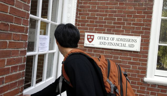 Freshman Winston Yan enters the Admissions Building at Harvard University September 12, 2006 in Cambridge, Massachusetts. Harvard is eliminating early admissions beginning next year because of criticism that it favors wealthier students and hinders those seeking financial aid since the deadlines for aid are much later. (Photo by Glen Cooper/Getty Images)