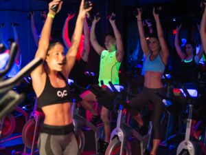 The author, in a blue sports bra, takes a class at Cyc (