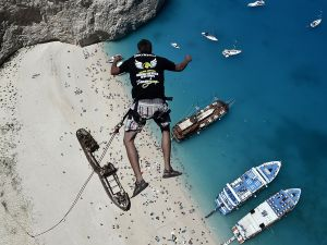 Lukas Michul, a member of the 'dream walker' group jumps from atop the rugged rocks overlooking the azure waters of Navagio beach, one of the Greece's most renowned leisure spots on the popular tourist island of Zakynthos on June 23, 2014. This is rope jumping -- part diving, part rock climbing, with a touch of engineering. The aim of the project is to dream jump in 80 places with most ravishing nature and architecture all over the world .They plan to stage their next leaps at a cave complex in Croatia, a French viaduct, skyscrapers in Las Vegas and Johannesburg, and the Grand Canyon. AFP PHOTO / LOUISA GOULIAMAKI (Photo credit should read LOUISA GOULIAMAKI/AFP/Getty Images)