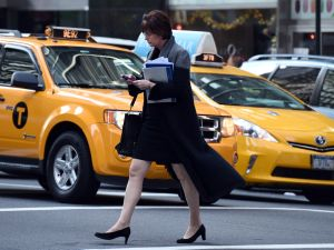 Hail a cab or ping your smart phone? A woman uses her smartphone while crossing a street corner on November 13, 2014 in New York. (DON EMMERT/AFP/Getty Images)